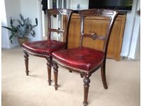 Dining Chairs. Two red leather upholstered and carved oak dining chairs.