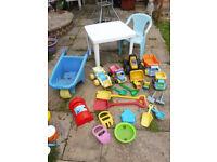 selection of sand toys, trucks wheelbarrow, table and chair