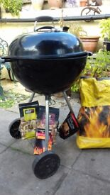 weber barbeque with coals and cleaner