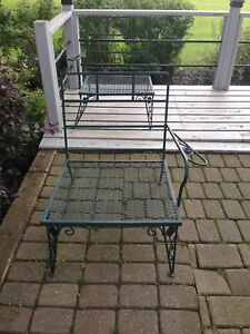 Two green metal outdoor chairs
