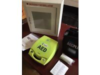 Defibrillator ( brand new) with wall mount box and lots of accessories.