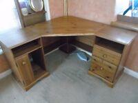 A corner, pine desk, in a reasonable condition.