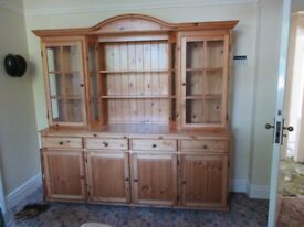 Pine dresser .top has glass cupboards and shelves botton has 4 drawers and cupboards