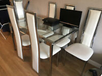 Stunning glass dining table that extends at both ends with 6 beautiful dining chairs