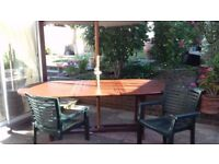 TEAK EXTENDING TABLE WITH LARGE UMBRELLA. 6 CHAIRS with matching cushions and Lazy Susan.