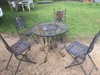 Wrought iron rustic garden table and 4 folding chairs