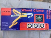 Uni-Com wheel clamp. In box. Unused