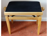 Piano stool in light wood with rise and fall mechanism.