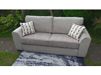 A New Designer 3 Seater Taupe Fabric Material Sofa. ( two available )