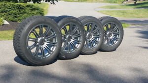 Four charcoal replica rims and tires with high profile lug nuts