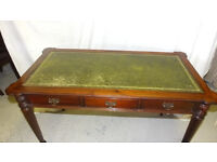 Writing desk with green leather inlaid top, tappered reed style legs, three solid wood drawers.