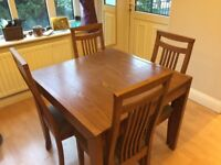 Extendable walnut dining table and matching chairs