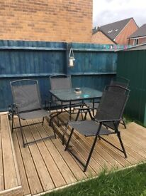 Black outdoor table and chairs with parasol