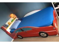 CAR BED WITH STORAGE SPACE AND A BOOK SHELF ALSO MATTRESS INCLUDED.