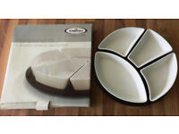 Porcelain Serving Dish Set - 4 shaped white dishes on black circular base.