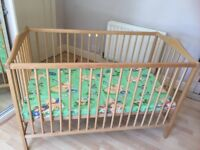 Wooden cot, with mattress. The mattress has a cover which is washable