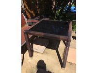 Brown rattan patio table with black glass top. Great condition. 80 x 80