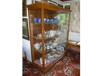 Large, mobile, shelved display cabinet.