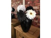 Large black glass vase with black and white flowers.