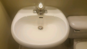 White pedestal sink with faucet