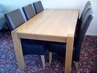 Solid oak dining table and six genuine leather chairs.