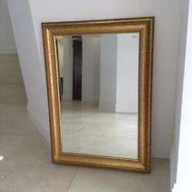 Gold framed wall mirror with bevelled edges.