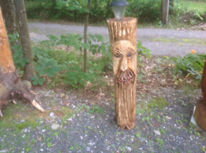 Chainsaw carved face on log with solar light