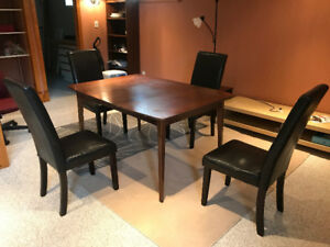 A brown dinner table with four chairs