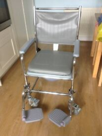 Wheeled commode with locking brakes and footplates. As new condition as hardly used.