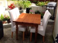 Pine table and 4 faux leather high back cream chairs.