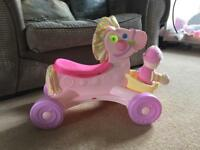 Little girls ride on pony with doll
