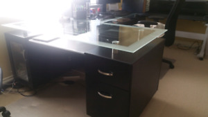 Glass top desk with filing draw and computer unit.