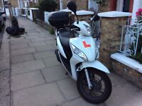 White honda vision for sale complete with top box, heated grips, and accessories