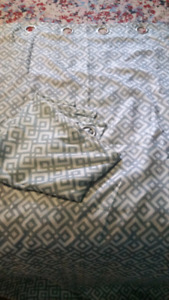 Teal and white pattern curtains, floor length.