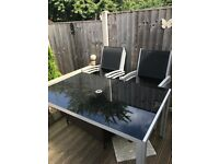 Six seater black glass table and chairs