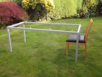 Glass top dining table supported on metal frame