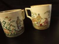 Pair of large Chinese beakers/mugs detailing two men smoking a pipe with floral design in abundance