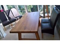 Oak dining table with five chairs.