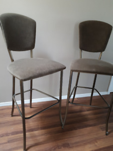 Two olive green bar stools with velvet surface