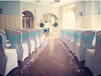 Wedding and event venue decor including chair covers and bows, bay trees, post box, centrepieces