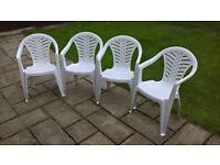 Four white patio chairs