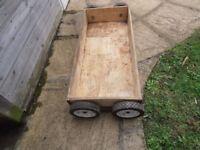 Reinforced wooden storage drawer on wheels.