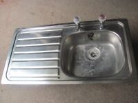Stainless steel sink with drainer and taps
