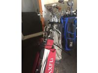 3 golf bags with clubs