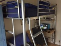 Single bunk bed frame with integrated desk and matching foldable chair.
