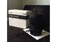 Mint condition Sigma art Lens, 35mm f 1.4 with a lens hood. Boxed and bag.
