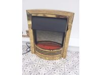 Gold electric fire place with white stones.