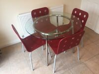 IKEA Glass/chrome-plated table with four chairs.