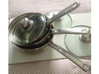 Set of three stainless steel saucepans