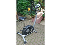 Exercise bike with extra-large padded seat and heart rate handlebar sensor.